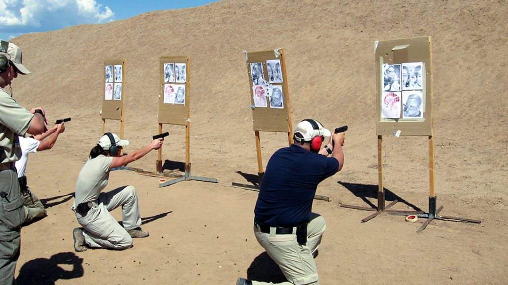 Students practice shooting from a kneeling position.